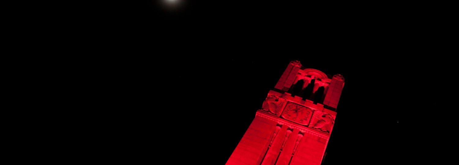 NC State bell tower at night lit up in red